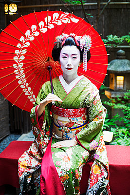 A woman dressed in the traditional geisha style, wearing a kimono and obi, with an elaborate hairstyle and floral hair clips, with white face makeup with bright red lips and dark eyes seated holding an umbrella.   - p1100m1185717 by Mint Images