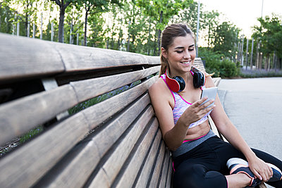 Pretty young woman in sportswear using smartphone and smiling on bench - p1166m2130086 by Cavan Images