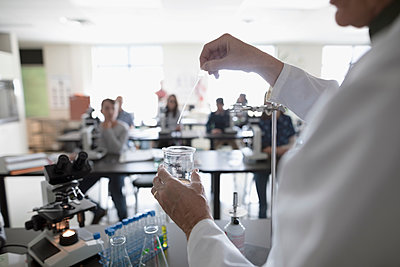 Students watching science teacher conducting scientific experiment in laboratory - p1192m1473272 by Hero Images
