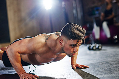 Serious man doing push ups in gym - p300m1581112 by gpointstudio