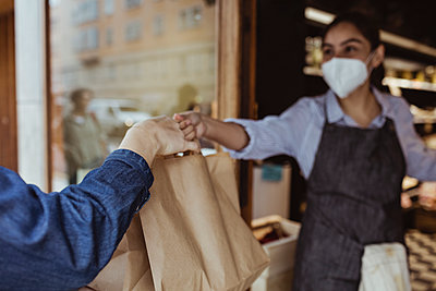 Sales woman giving take away food to customer at deli shop during pandemic - p426m2270508 by Maskot