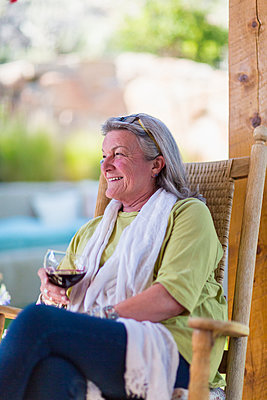 Caucasian woman drinking wine on porch - p555m1411396 by Marc Romanelli