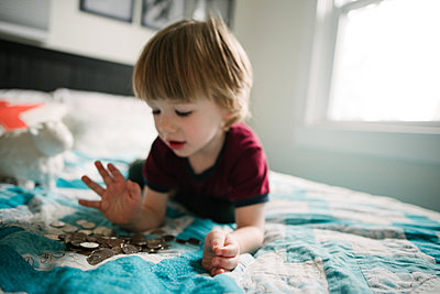 Boy counting coins on bed - p924m2074225 by Viara Mileva