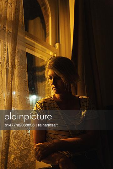 Woman sitting at the window - p1477m2038893 by rainandsalt