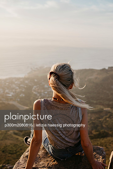 South Africa, Cape Town, Kloof Nek, woman sitting on rock at sunset - p300m2080816 by letizia haessig photography