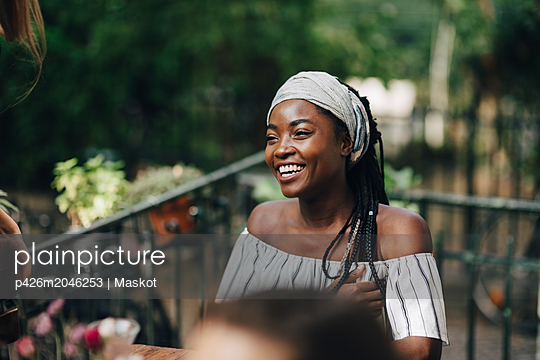 Happy young woman looking away while sitting in balcony during party - p426m2046253 by Maskot