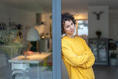 Portrait of woman leaning against terrace door at home - p300m2080611 von Joseffson