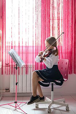 Girl sitting at the window at home playing violin - p300m2102905 by Ekaterina Yakunina