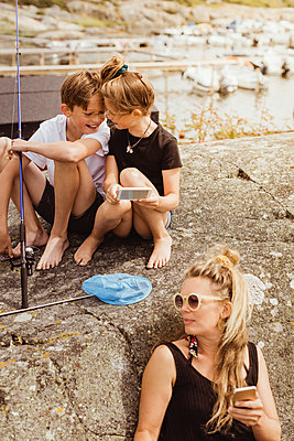 Mother and children with smart phone spending leisure time at harbor during picnic - p426m2238349 by Maskot