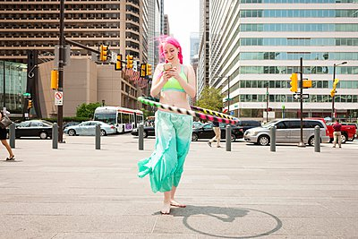 Young woman hoola hooping whilst reading smartphone text, Philadelphia, Pennsylvania, USA - p924m1047968f by Zave Smith