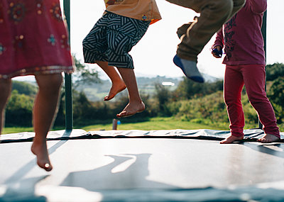Children jumping on the trampoline - p972m1160351 by Rowan Thornhill