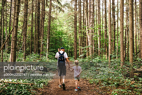Man holding hands of daughter while hiking in woodland - p300m2202747 by Jennifer van Son