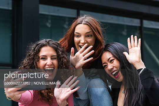 Cheerful friends waving hand to video call on mobile phone - p300m2277382 by NOVELLIMAGE