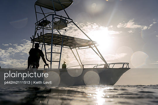 Silhouette of a man on the deck of a boat on the water against a blue sky with sunlight; Bay Islands Department, Honduras - p442m2111513 by Keith Levit