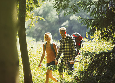 Couple with backpacks hiking in sunny woods - p1023m1402877 by Paul Bradbury