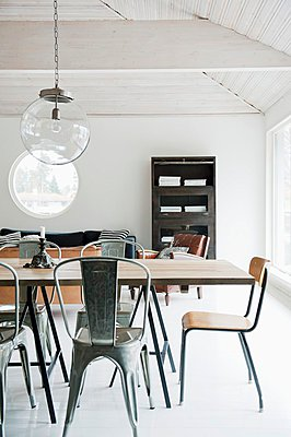 Minimalist, open-plan interior with industrial-style furniture; spherical glass lamp in front of porthole window of same size - p1183m995803 by Bjernsdotter, Magdalena