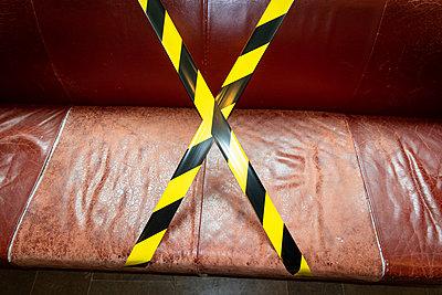 Barrier tape on leather couch - p1418m2263750 by Jan Håkan Dahlström