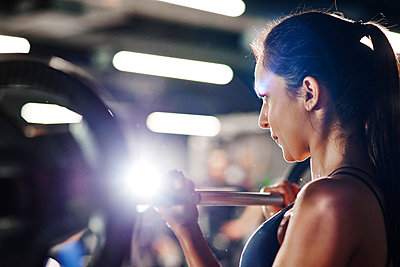 Woman lifting barbell in gym - p300m1581349 by gpointstudio
