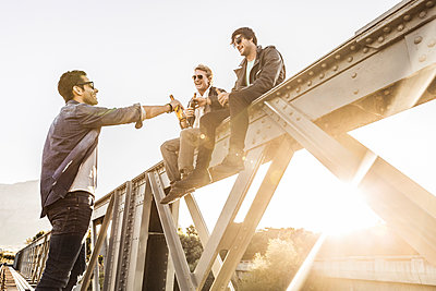 Three men drinking beer on an old railway bridge - p300m2180844 by Floco Images