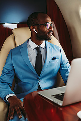 Young businessman looking away with laptop on table in airplane - p300m2256388 by OneInchPunch