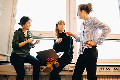 Low angle view of confident female colleagues discussing against window at creative office - p426m1588461 by Maskot
