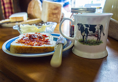 Jam and bread on tea table with mug of tea - p429m2019518 by Seb Oliver