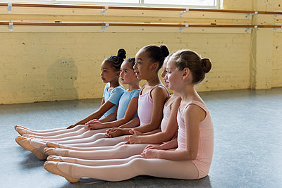 Girls sitting in a row on floor of ballet studio - p555m1491095 by Mark Edward Atkinson