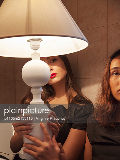 Two women with lamp in bathromm - p1105m2133118 by Virginie Plauchut