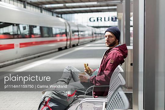 junger Mann wartet am Bahnhof - p1114m1159750 von Carina Wendland