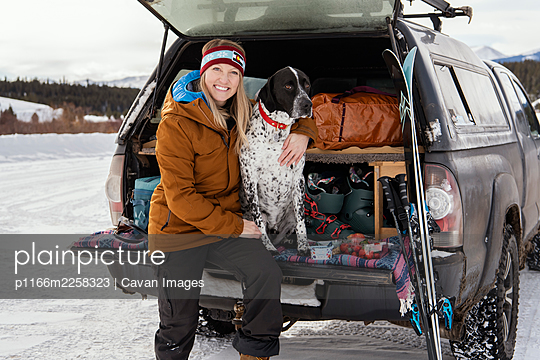 Smiling woman with dog in off-road vehicle during winter - p1166m2258323 by Cavan Images
