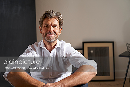 Portrait of smiling mature man relaxing at home - p300m2155696 by Isabella Bellnini