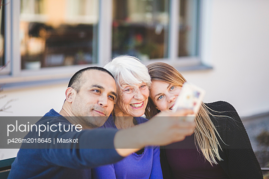 Multi-generation family smiling while taking selfie outside nursing home - p426m2018645 by Maskot