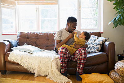 Affectionate father in pajamas cuddling with baby son on living room sofa - p1023m2016551 by Sam Edwards