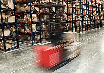 Blur of a motorized stock picker between aisles of cardboard boxes on pallets stacked on large racks in a large distribution warehouse. - p1100m1575489 by Mint Images