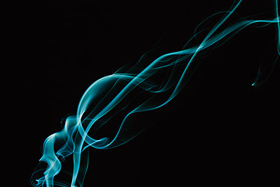 Close-up of turquoise smoke against black background - p1166m2024908 by Cavan Images
