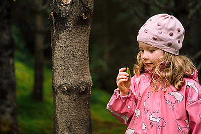 Adorable girl studying leaf in forest - p1166m2130823 by Cavan Images