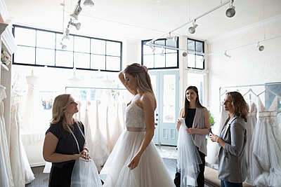 Bride and friends at wedding dress fitting in bridal boutique - p1192m1583300 by Hero Images