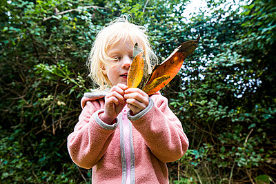 Blond little girl playing with leaves - p300m2180235 by Irina Heß