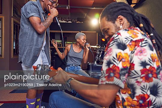 Musicians practicing in recording studio - p1023m2190259 by Trevor Adeline
