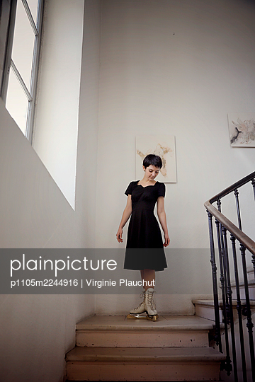 Woman in black dress and skates in the stairwell - p1105m2244916 by Virginie Plauchut