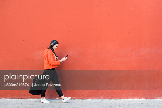 Young dancer walking and using the phone and headphones in front of a red wall - p300m2103741 by Josep Rovirosa