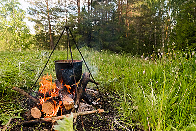 Food being cooked in container on campfire at forest - p1166m1541768 by Cavan Social