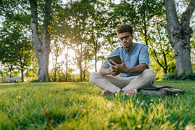Young man sitting in park using mobile device - p300m1535757 by Kniel Synnatzschke