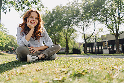 Smiling redheaded woman sitting on grass verge - p300m2140842 by Kniel Synnatzschke