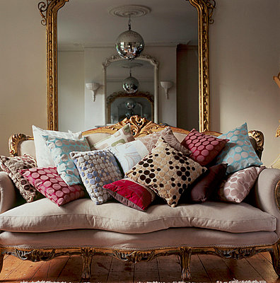 Decorative upholstered vintage sofa piled with patterned fabric cushions in a living room with large mirror - p349m695236 by Emma Lee