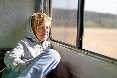 Boy sitting in campervan looking out of window, Polonio, Rocha, Uruguay, South America - p429m1519597 by Stephen Lux