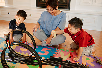 Asian grandmother playing with grandsons - p555m1408679 by Shestock