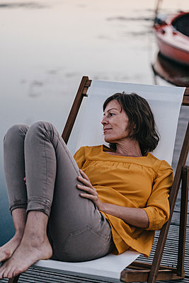Woman relaxing on canvas chair at Lake Baldeneysee - p586m1172057 by Kniel Synnatzschke