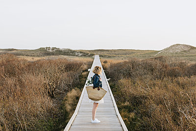 Lone young woman looking out from coastal dune boardwalk,  Menemsha, Martha's Vineyard, Massachusetts, USA - p924m2058148 by Lena Mirisola