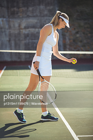 Woman with tennis racket ready to serve